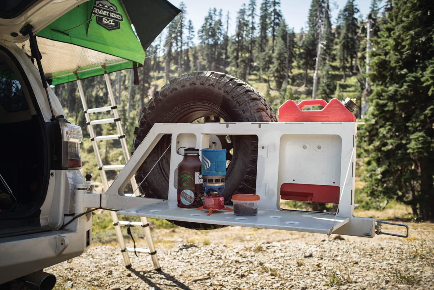 CBI's Swing Away Tire Carrier is outfitted with an optional swing-down camp table for extra work space.