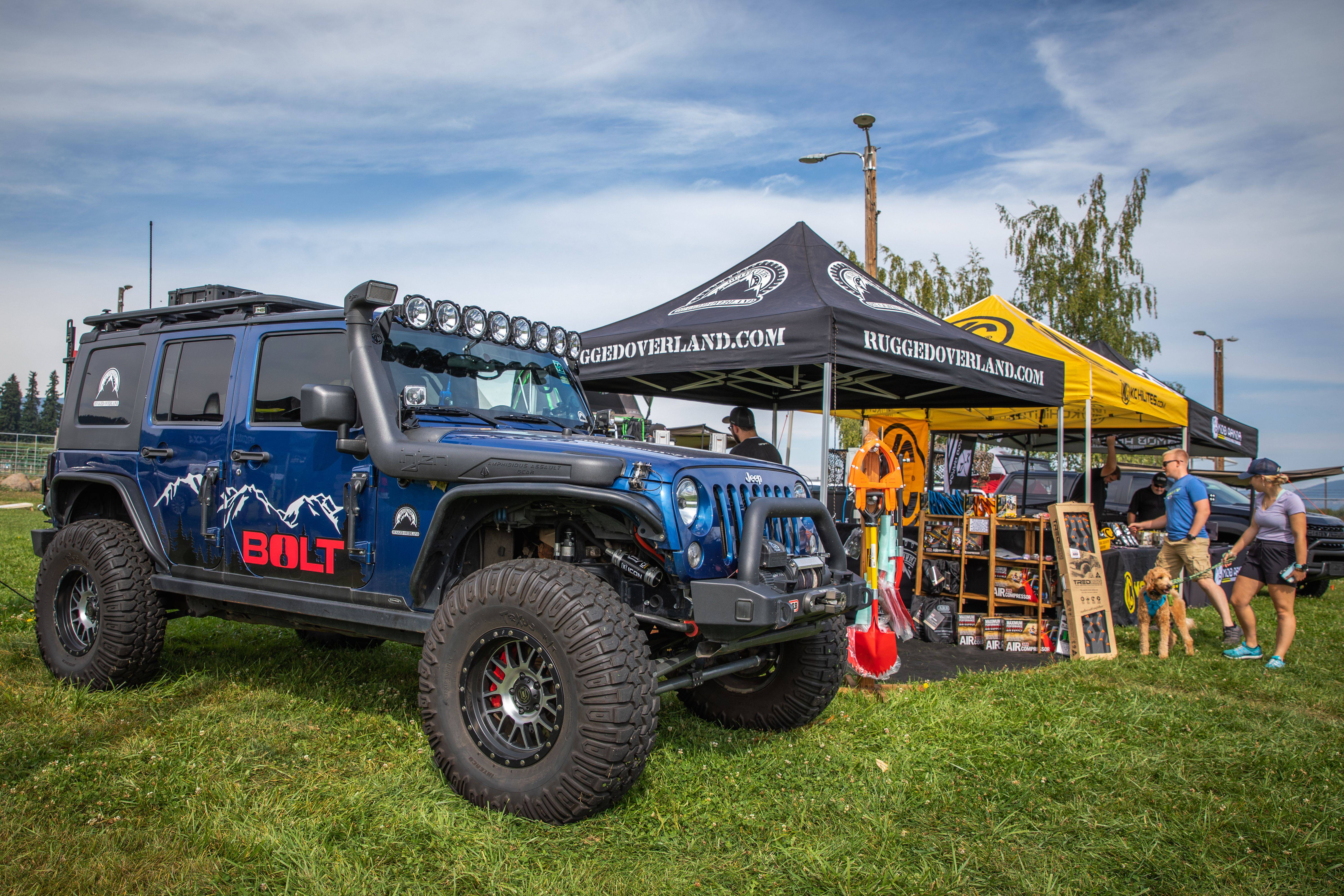 Toyo Tires Trailpass: Rugged Overland.com booth next to blue Jeep Wrangler