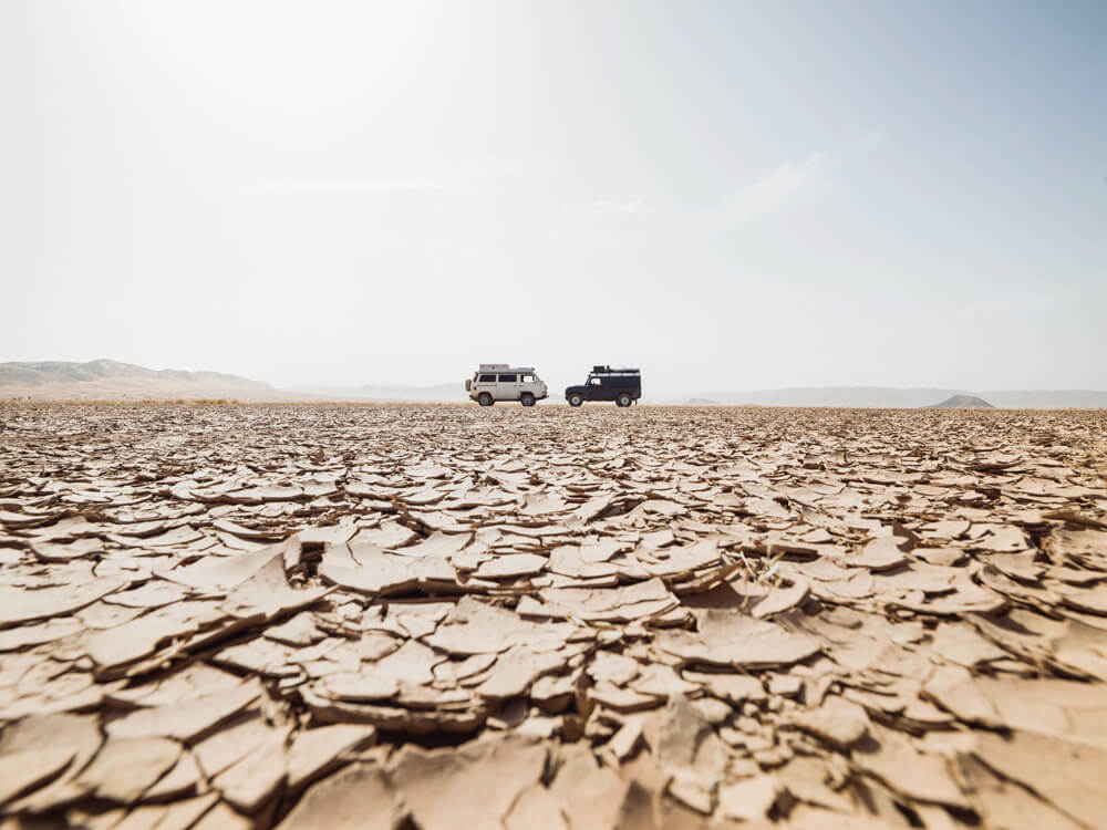 Vehicles in distance in desert with dry cracked dirt terrain.