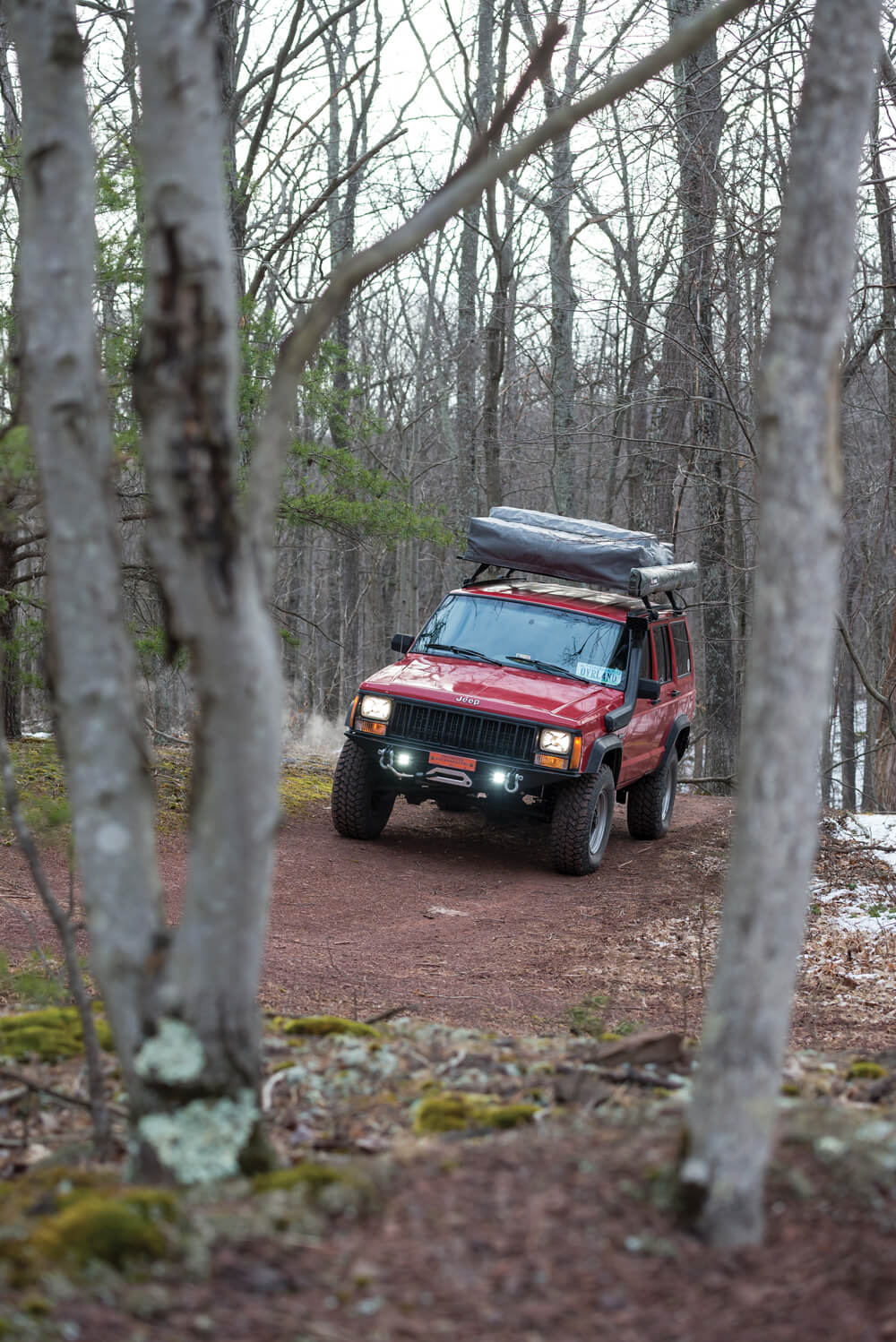 1994 Jeep Grand Cherokee XJ driving in the woods with an RTT