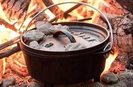 Dutch oven in a camp fire with coals on top of the lid and flames in the background