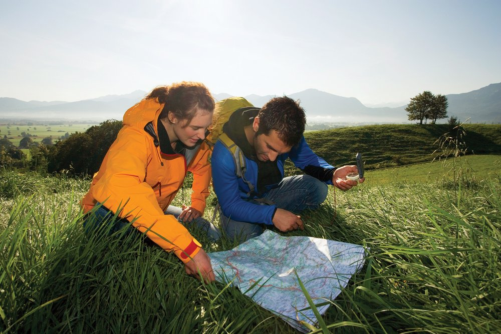 Couple using a compass and map for backcountry navigation