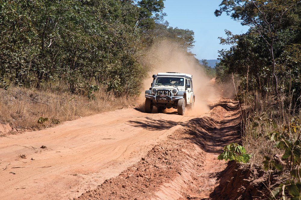 Jeep traveling down dirt road in Zambia