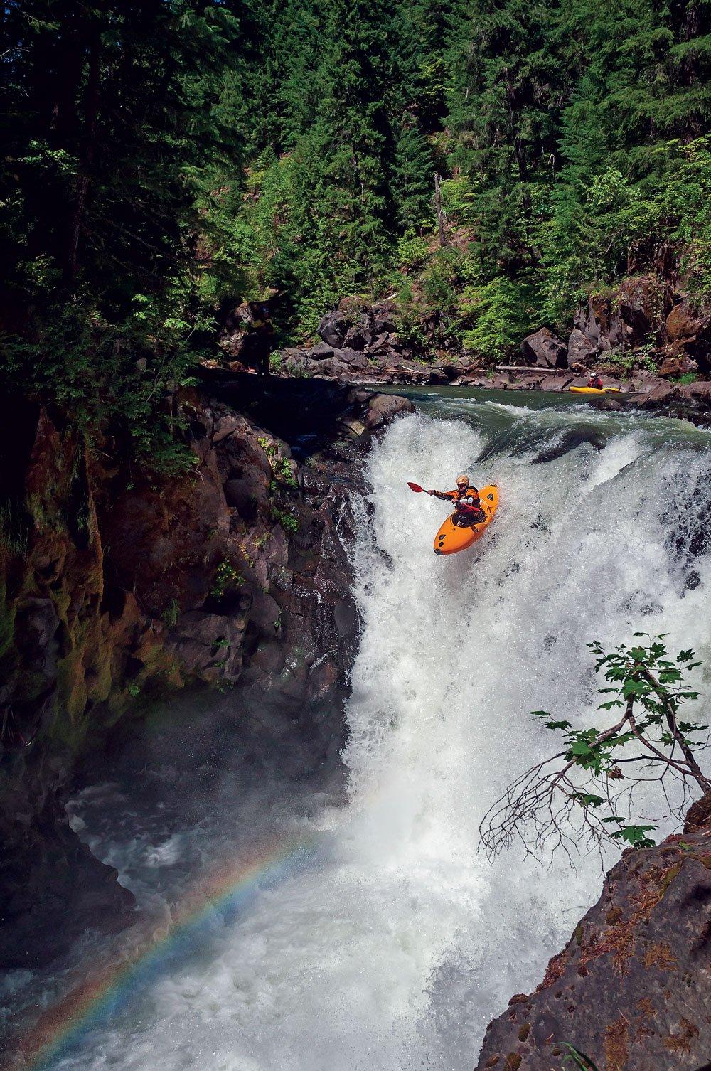 kayaker heading toward a rainbow at the bottom of a waterfall