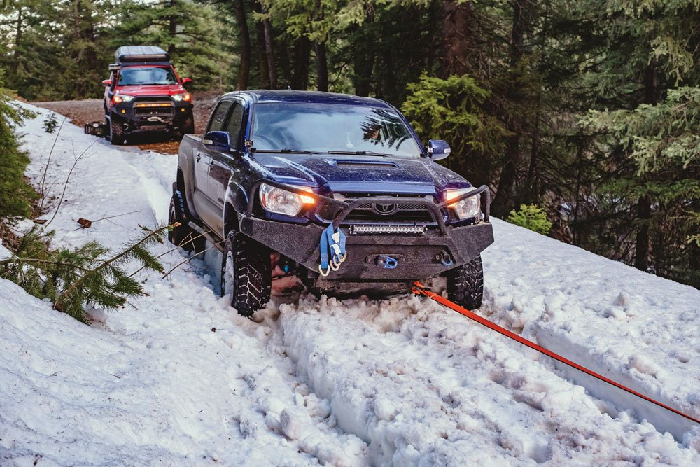 Toyota being pulled out of snow using a recovery rope