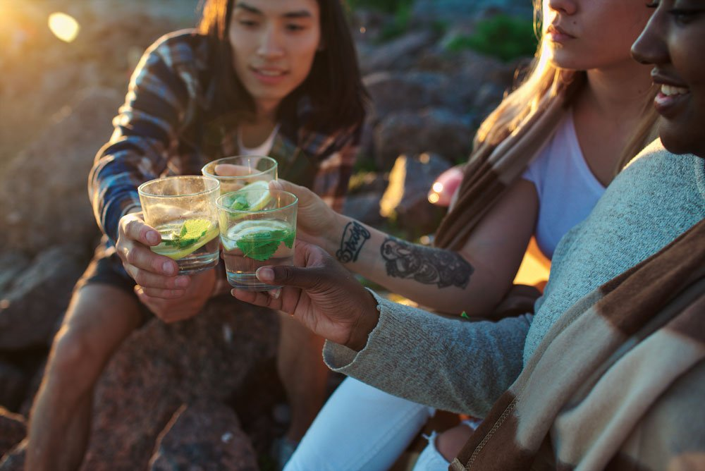 Three people cheers their camping cocktails