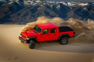Red Jeep Gladiator turns up sand in desert.