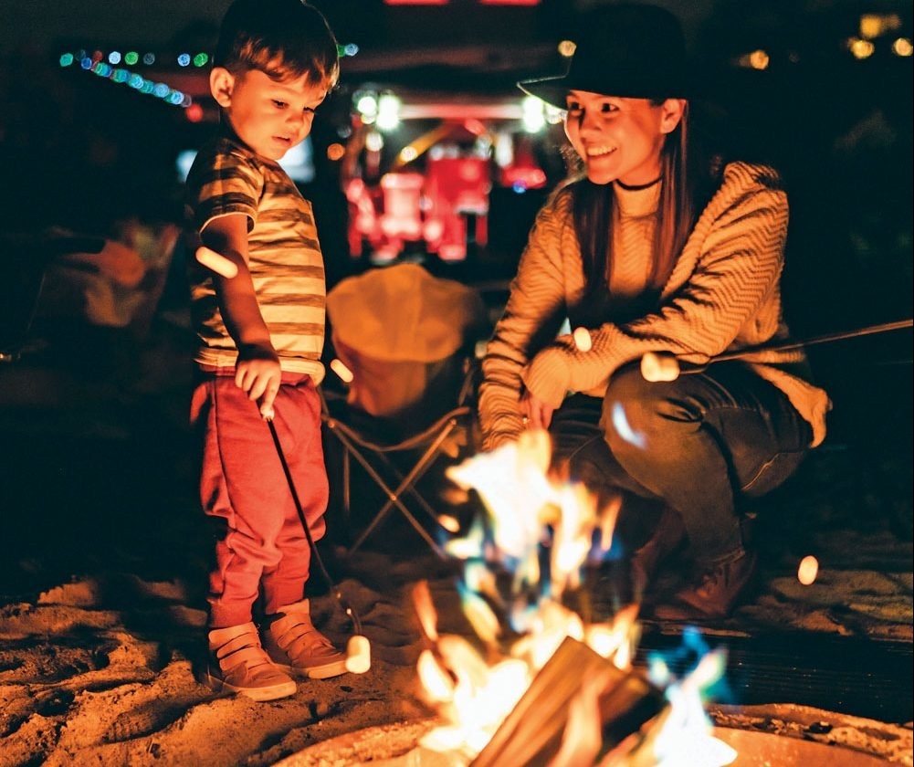 Mother and son roasting marshmallows at the campfire