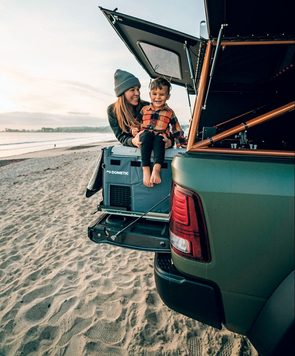 Mother and son on the tailgate of the AEV Prospector XL at the beach