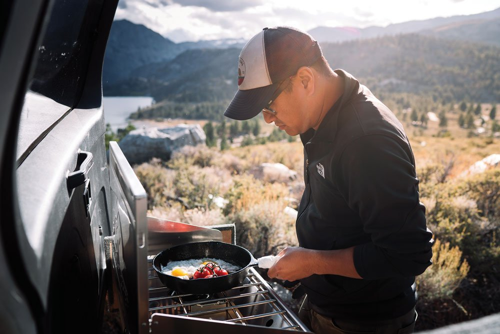 Man cooking in cast iron pan on a Camp Chef Mountaineer