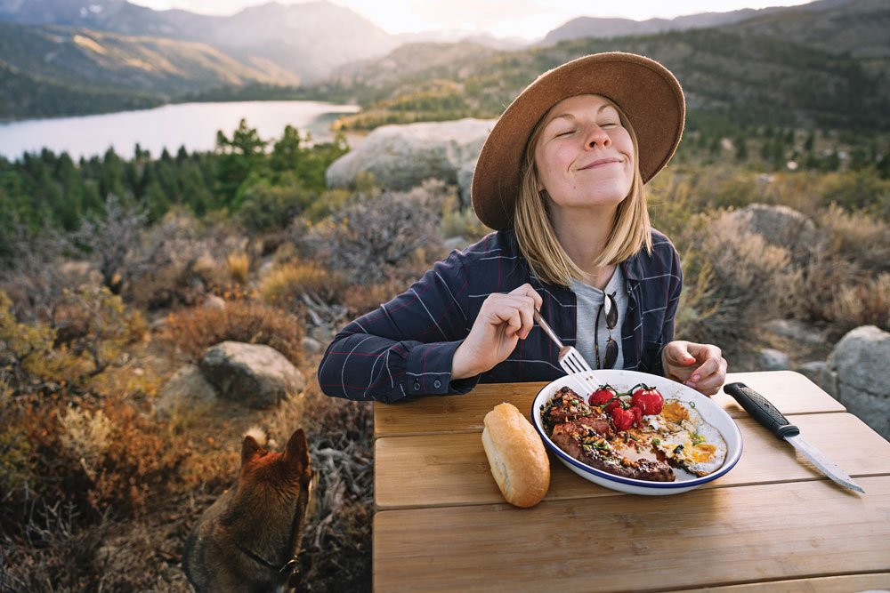 Woman enjoys Vietnamese Steak and Eggs while camping