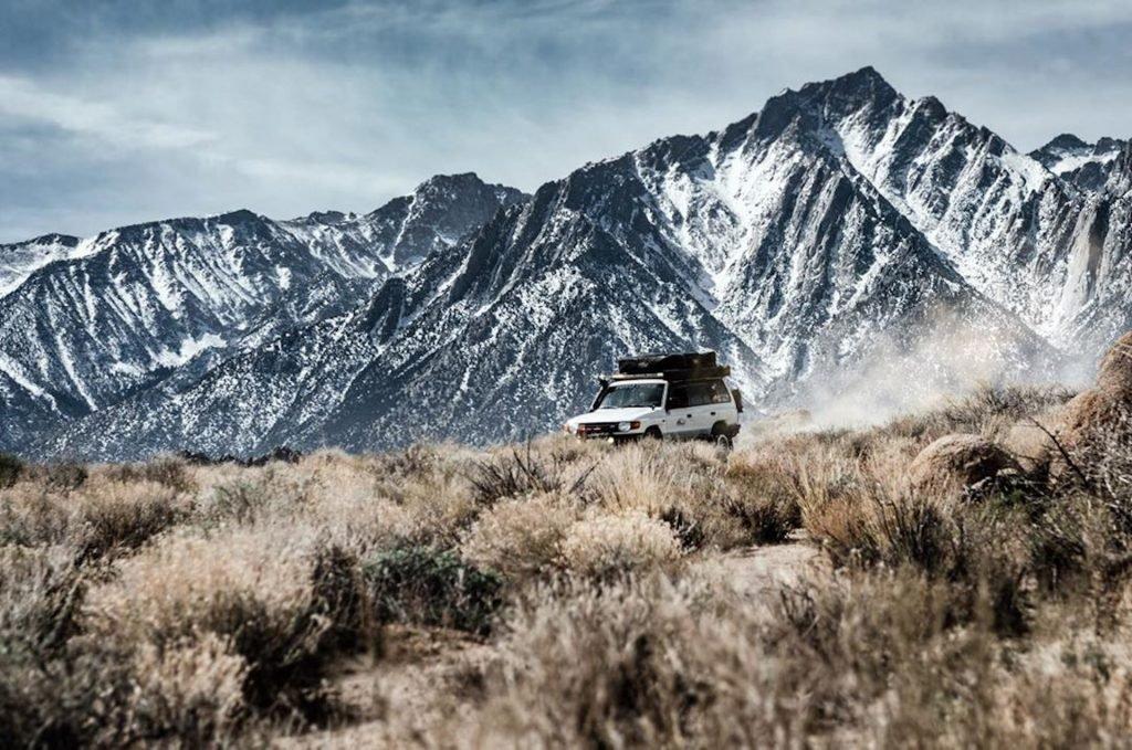 White Misubishi Montero drives through brush with snowy mountains behind.