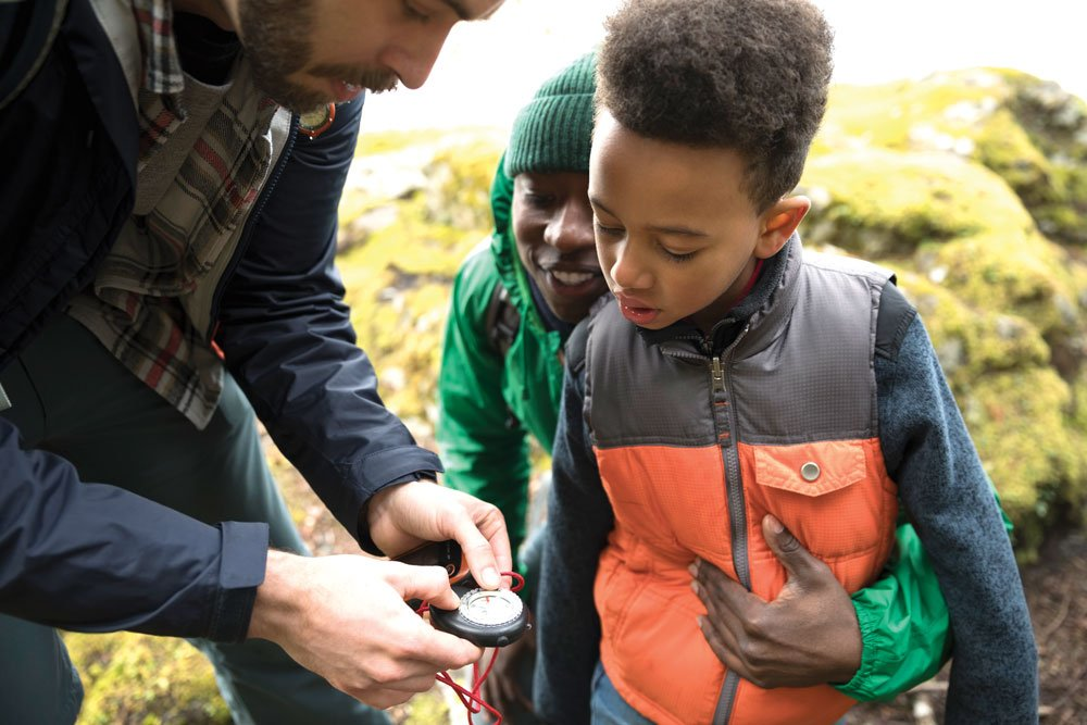 Man showing a child how to use a compass
