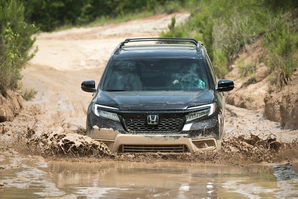 2019 Honda Passport Elite SUV driving into a muddy lake