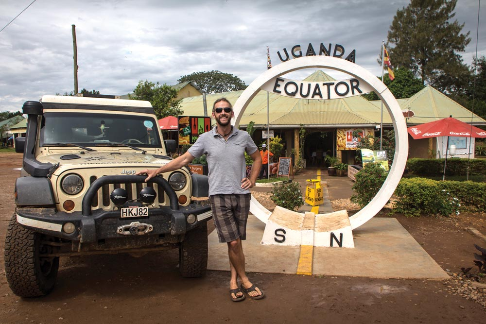 Dan Grec poses in front of the Uganda Equator line sign
