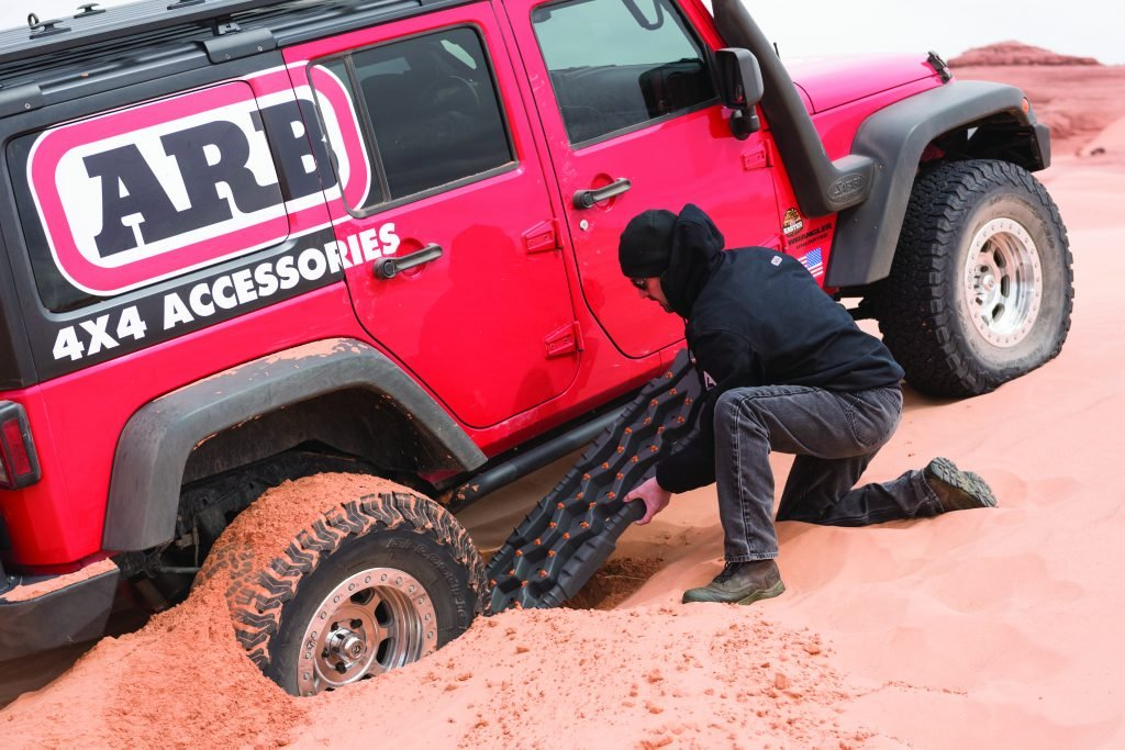 Man using recovery board to get stuck vehicle