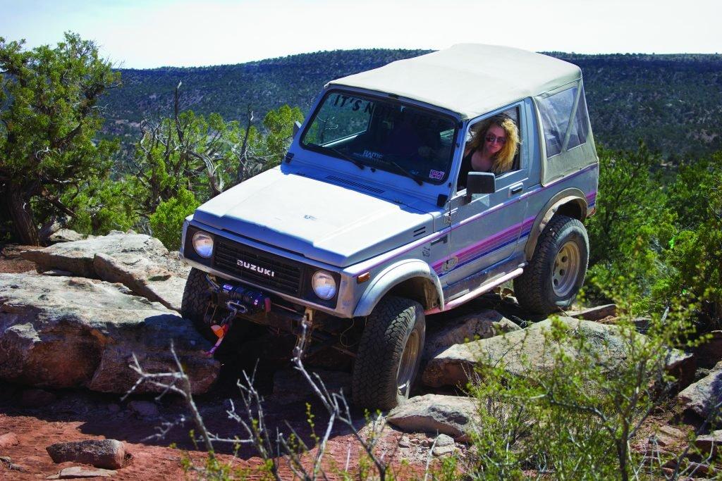 Women driving Suzuki Samurai over smooth rock ledges