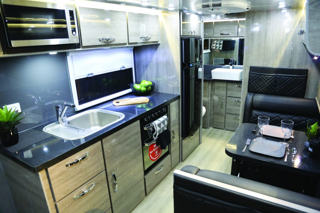 The camper is equipped with a kitchen that has a fullsize refrigerator