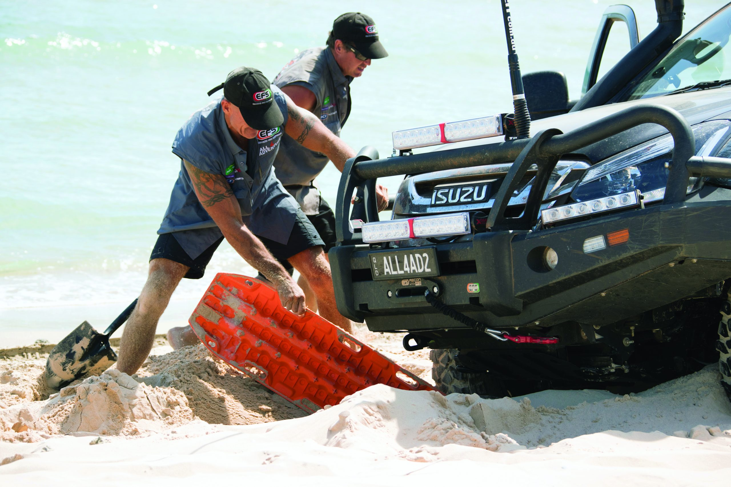 Two people using a recovery board for a stuck vehicle
