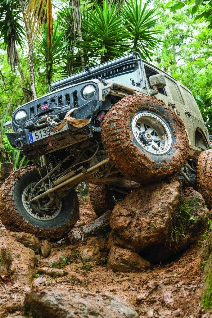 Jeep climbing giant, muddy rocks