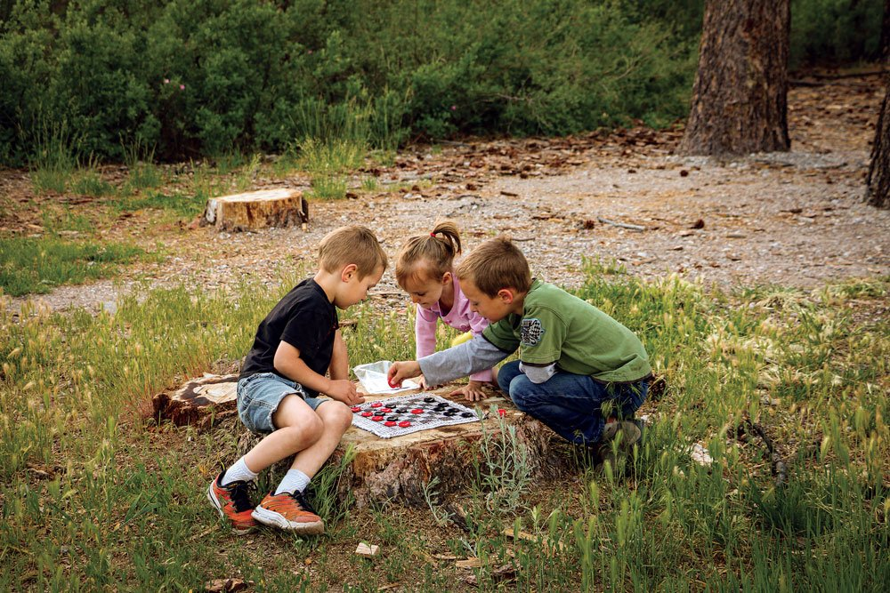 Three kids playing checkers using a log as a table