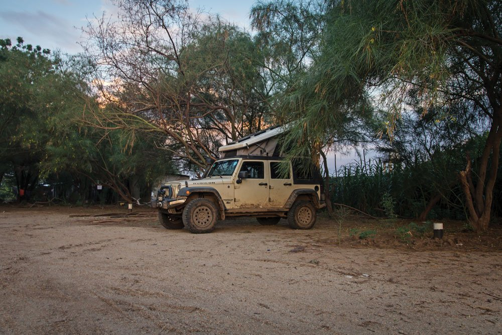The Jeep is tucked into the trees in a camp spot found in Ethiopia