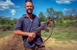 World traveler Dan Grec poses with AK-47 in Ethiopia.