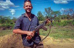 World traveler Dan Grec poses with AK-47 in Ethiopia.