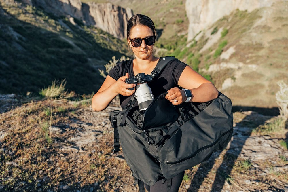 A woman utilizes the perfect camera bag