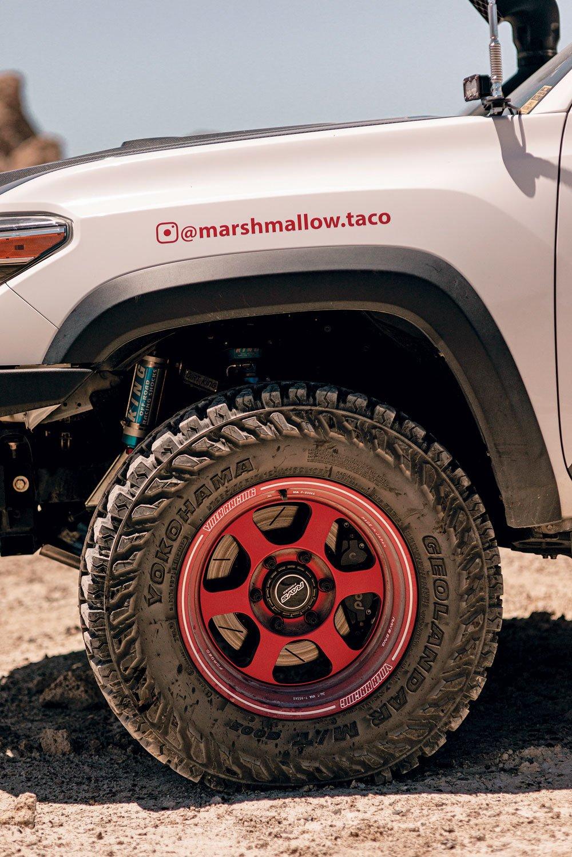 A Wilwood Big Brake kit sits behind red Volk Racing TE37XT wheels that are wrapped in Yokohama Geolander tires
