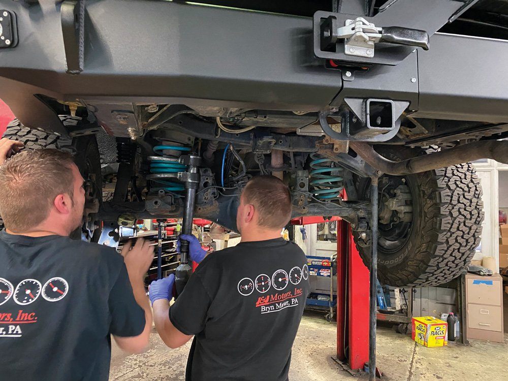 Two guys from J&J Motors installing the Load-Leveling System