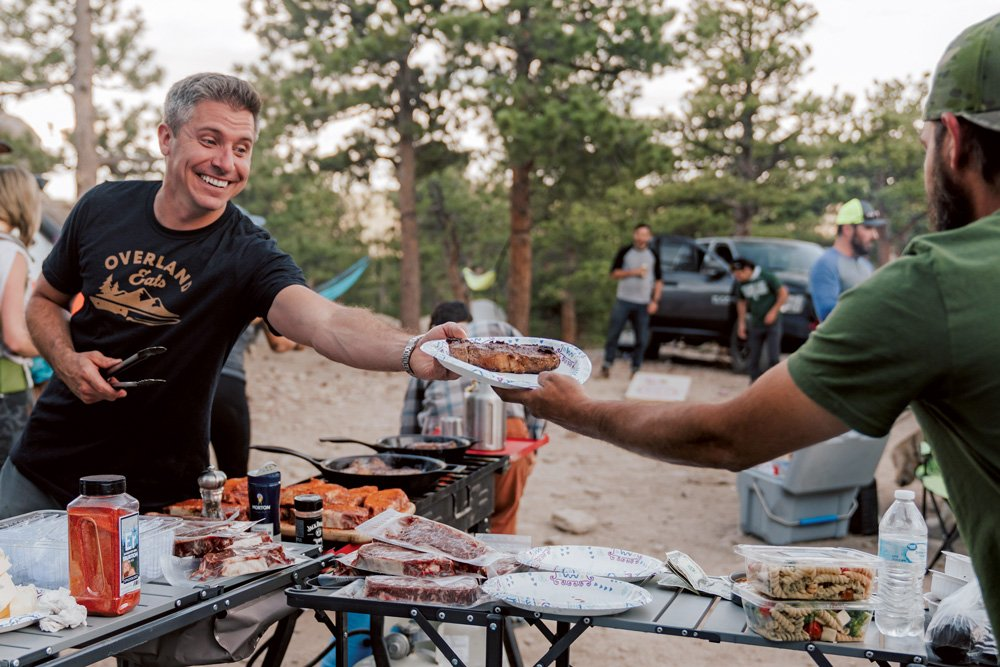 Nicosia smiling as he serves a guest at an Overland Eats pop-up dinner