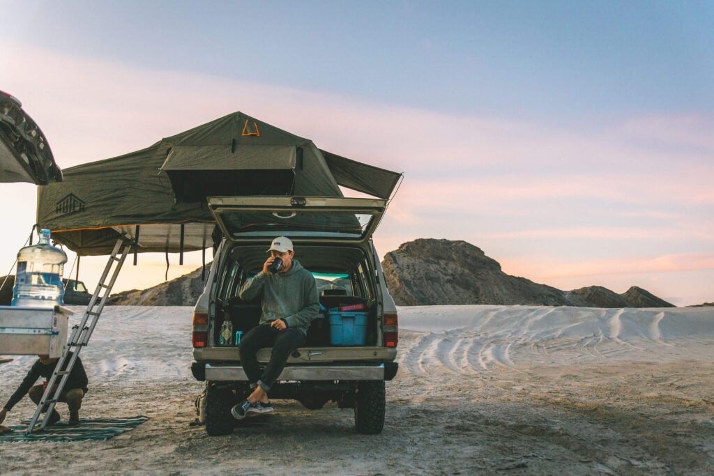 Land Cruiser with roof top tent and man drinking from cup.