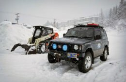 Pajero next to running skit steer in Whittier, Alaska