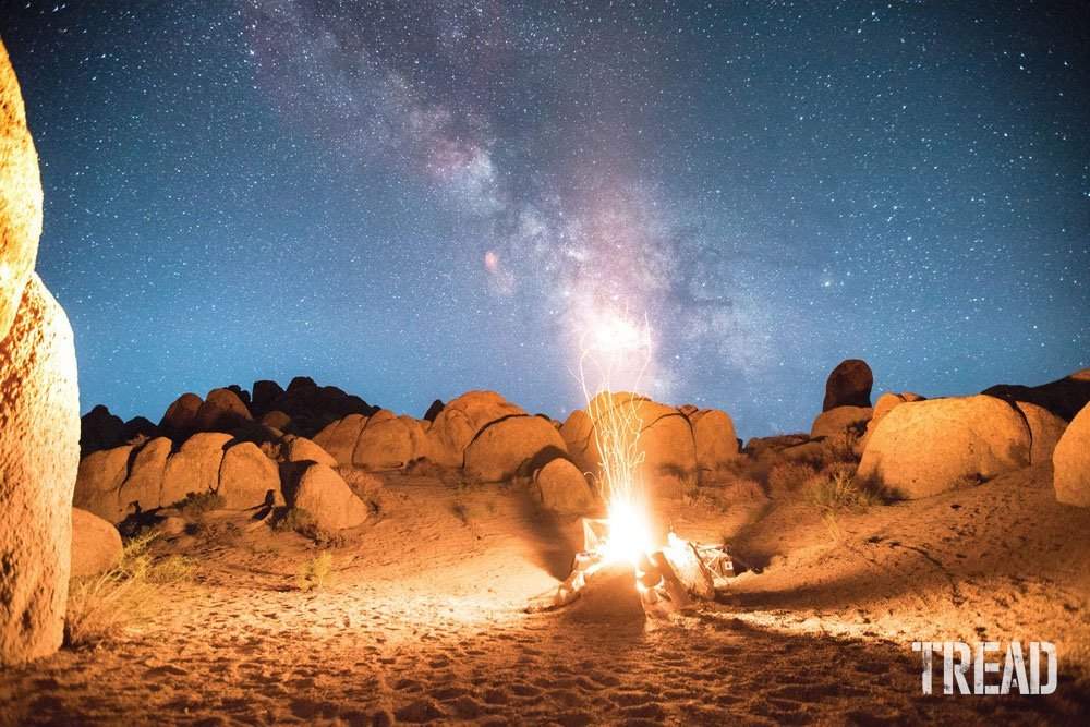 Campfire against large rocks and star-filled night sky