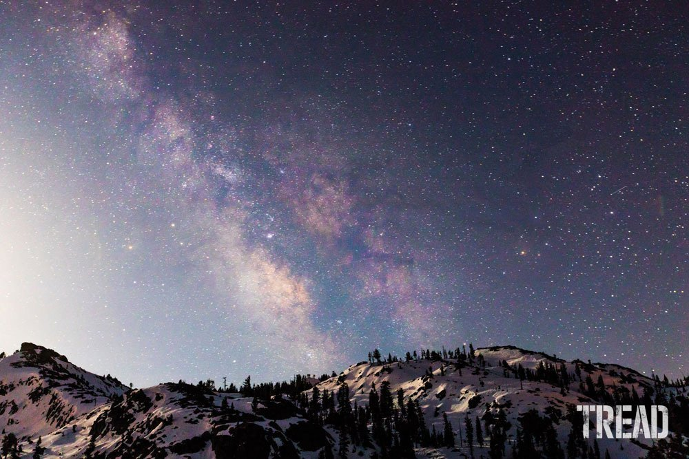 Snow and tree-filled mountainside with starry night sky