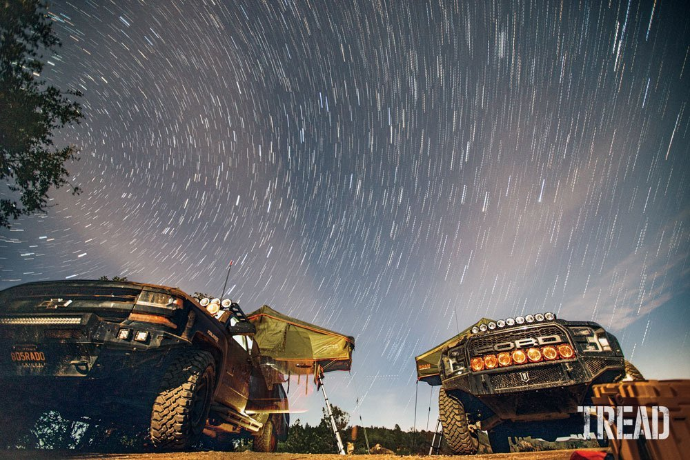 Two overlanding trucks with rooftop tents with starry night sky