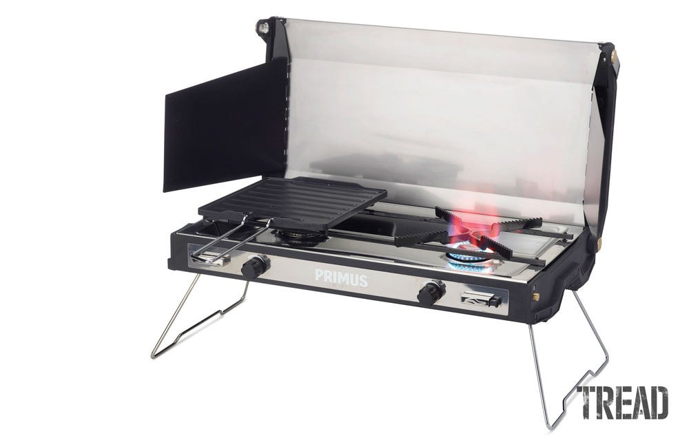 Primus Tupike portable stove with lid open to show two burners and included grill pan.