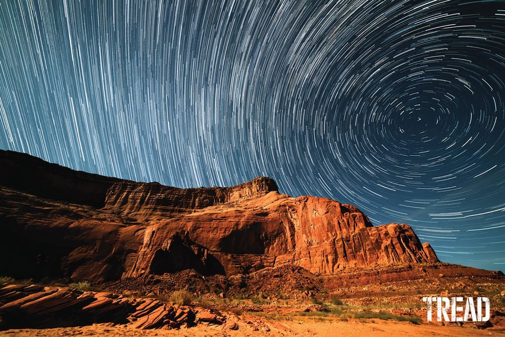 Time lapse of starry night sky against rock wall