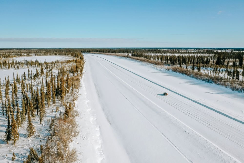 A truck drives on a snowy road in Arctic Canada from Inuvik to Aklavic.
