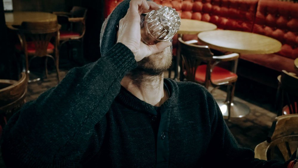 Man drinking the Sour Toe Cocktail in a bar.