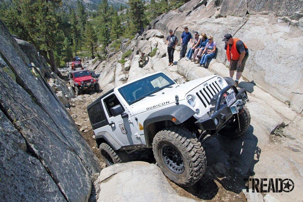 White Jeep climbs rocky terrain for the Sierra Trek with Cal4Wheel group.