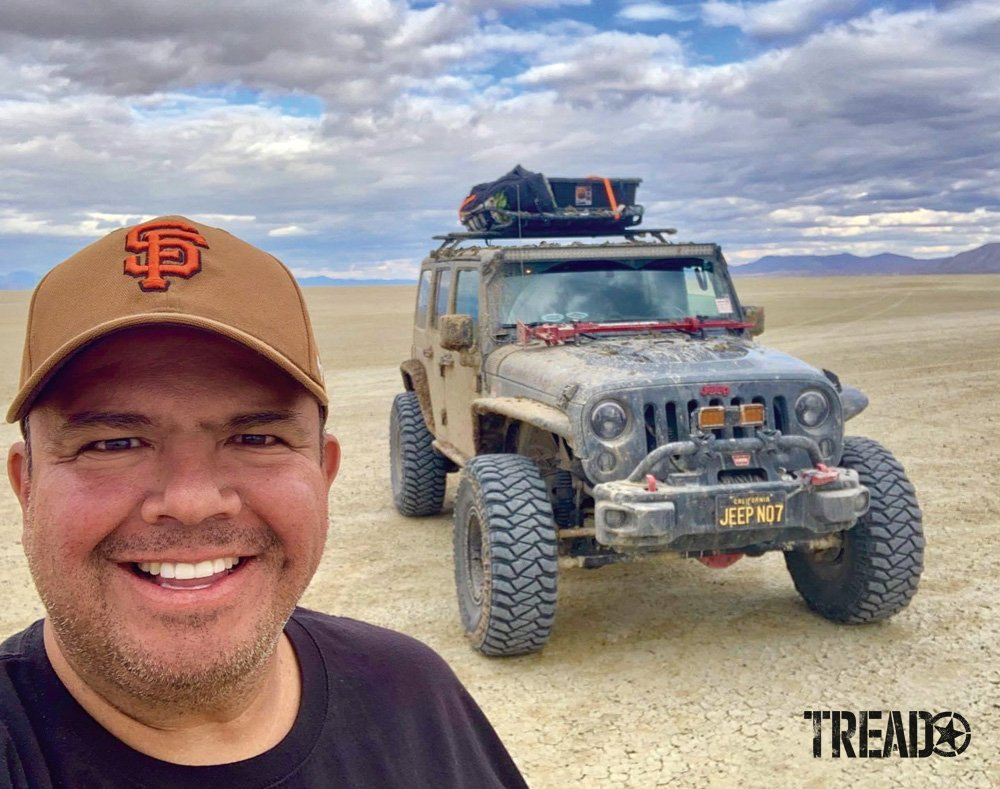 Roger Salazar stands near Jeep on dry lake bed.