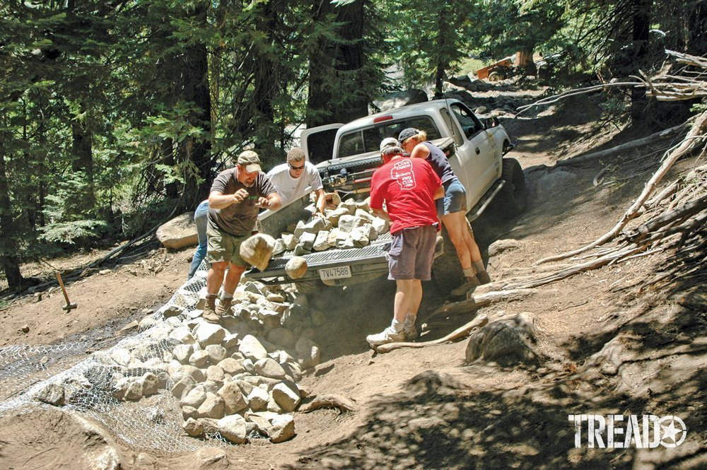 Men cleaning up a trail by adding rocks from the back of a truck bed.