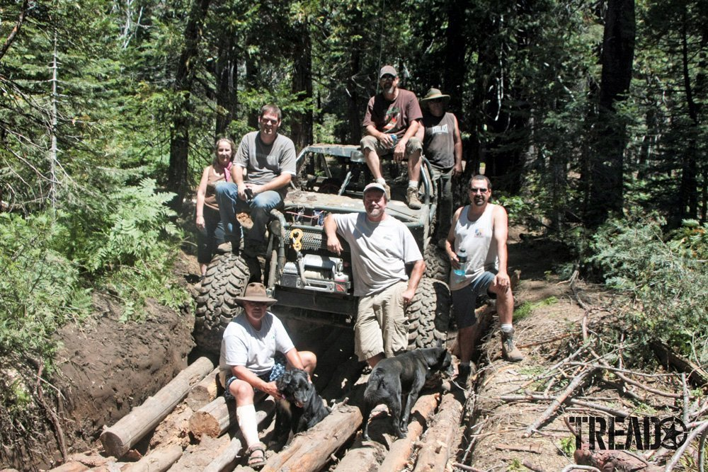 Friends of the Rubicon and the Rubicon Trail Foundation standing in front of customized 4x4 sitting on logs supporting land-use activism.