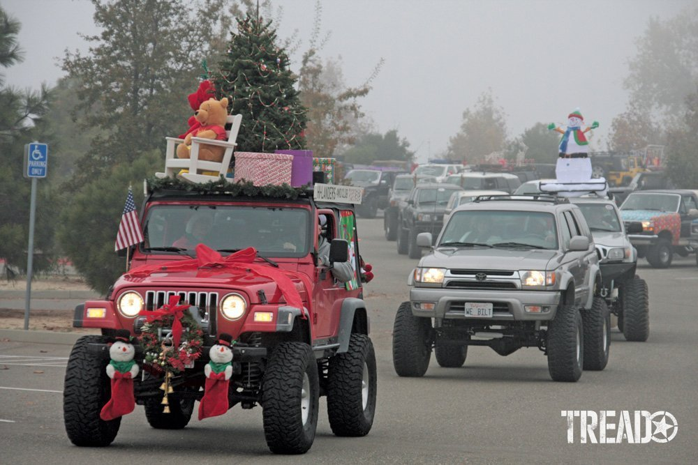 Various 4x4s are driving down the street, decorated with Christmas trees and presents, during a holiday parade
