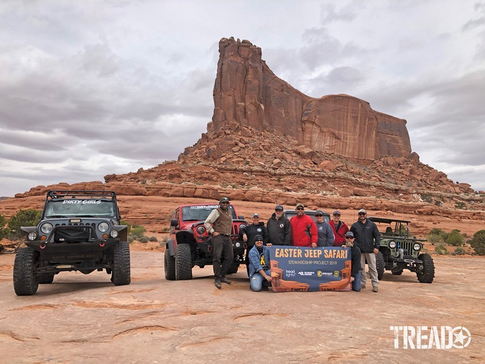 Tread Lightly! members and others hold banner in front of Jeeps in Moab during a stweardship project at Easter Jeep Safari 2019.