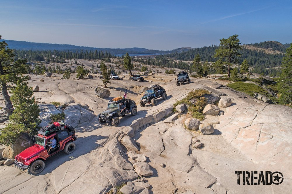 Different customized 4x4 vehicles driving on rocky off-road trail