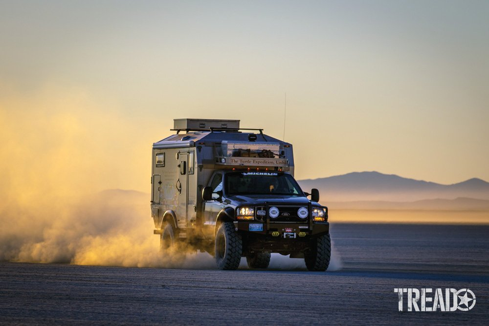 Expedition camper driving on dried lakebed