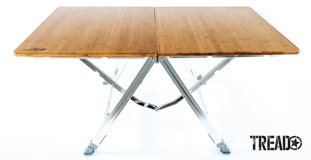 The Kovea Bamboo One Action Table folds in half with its chrome legs nesting inside of the tabletop.